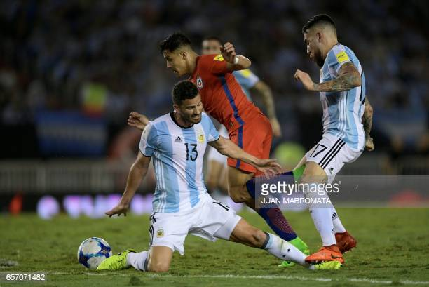 Chile's forward Alexis Sanchez dribbles past Argentina's Mateo Mussacchio and Nicolas Otamendi during their 2018 FIFA World Cup qualifier football...