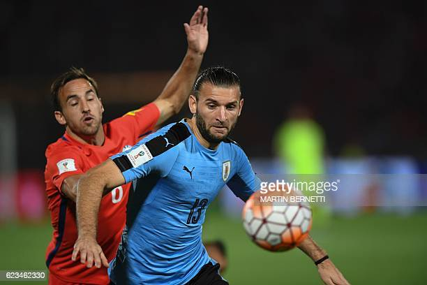 Chile's forward Jose Fuenzalida and Uruguay's Gaston Silva vie for the ball during their 2018 FIFA World Cup qualifier football match in Santiago on...