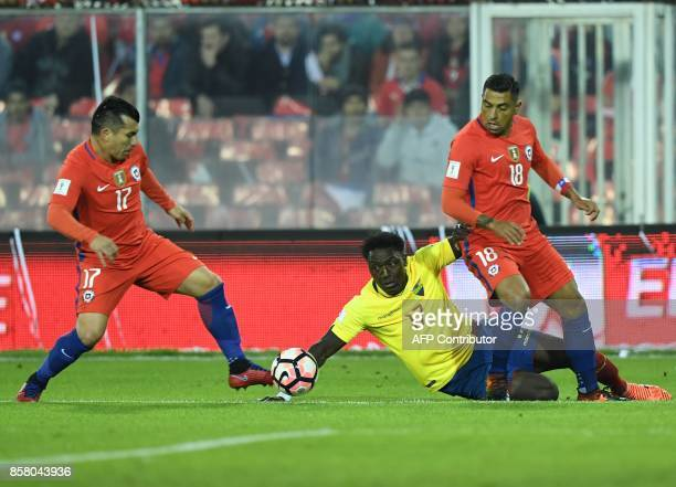 Chile's Gary Medel and Gonzalo Jara vie for the ball with Ecuador's Roberto Ordonez during their 2018 World Cup qualifier football match in Santiago...