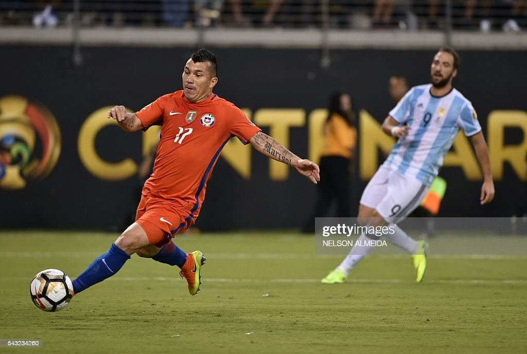 Chile's Gary Medel (L) drives the ball next to Argentina's Gonzalo Higuain during the Copa America Centenario final in East Rutherford, New Jersey, United States, on June 26, 2016. / AFP / NELSON