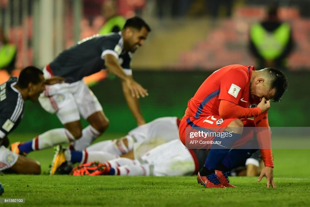 Chile's Gary Medel (R) gestures after Paraguay's Richard Ortiz (covered) scored a goal during their 2018 World Cup qualifier football match, in Santiago, on August 31, 2017. / AFP PHOTO / Martin BERNETTI