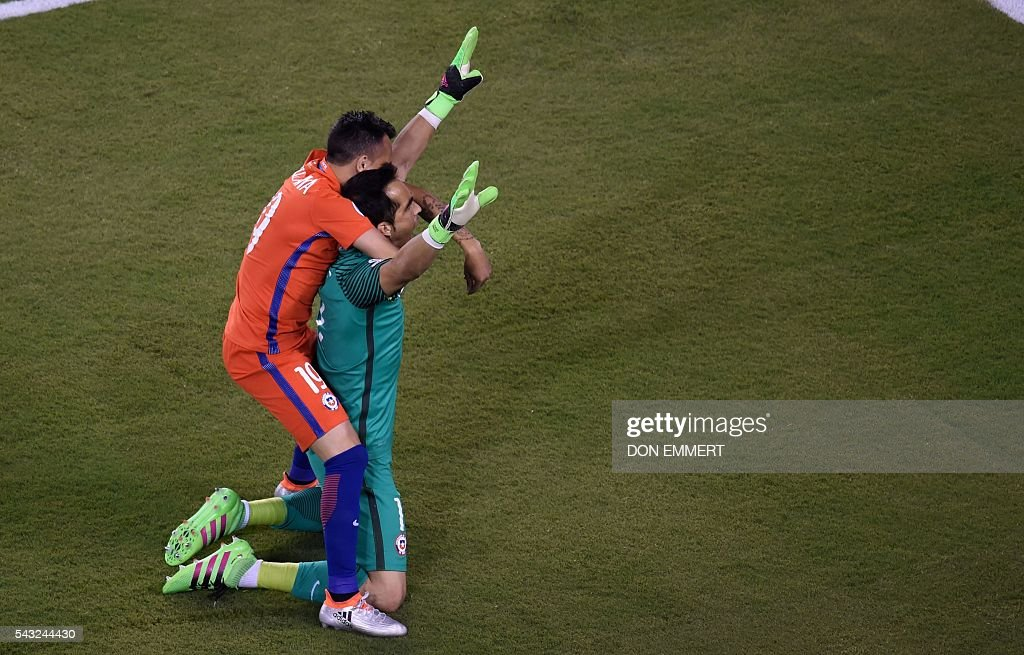 Chile's goalie Claudio Bravo (R) and Chile's Fabian Orellana celebrate after defeating Argentina and winning the Copa America Centenario final in East Rutherford, New Jersey, United States, on June 26, 2016. After extra-time, Chile win penalty shoot-out 4-2. / AFP / Don EMMERT