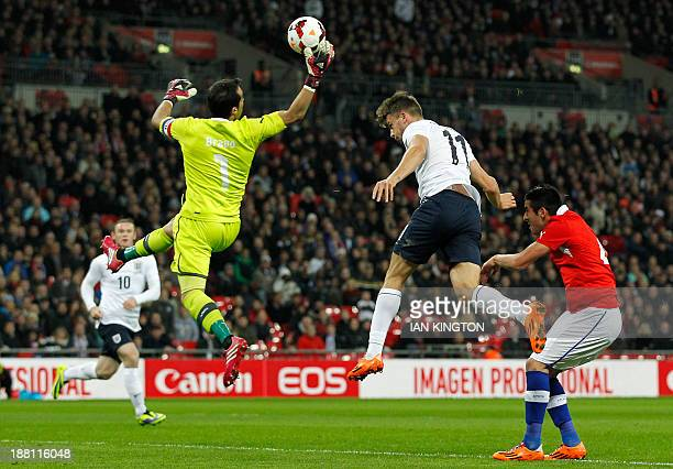 Chile's goalkeeper Claudio Bravo catches the ball ahead of England's striker Jay Rodriguez during the international friendly football match between...