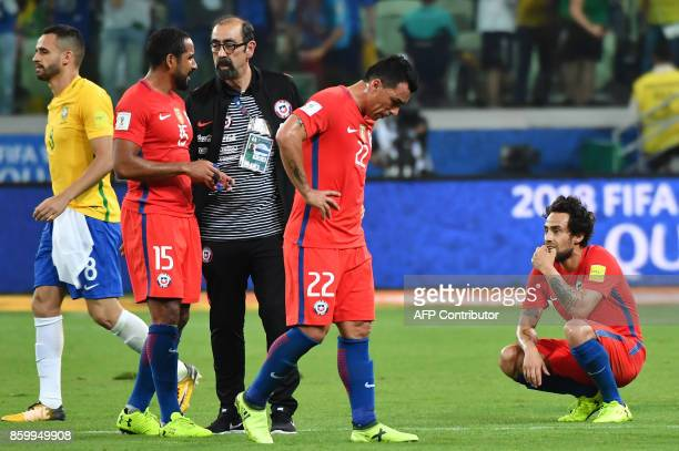 Chile's Jean Beausejour Esteban Paredes and Jorge Valdivia show their dejection after being defeated by Brazil in a qualifier match and missing the...