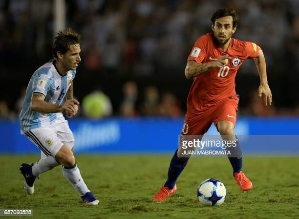 Chile's Jorge Valdivia and Argentina's Lucas Biglia vie for the ball during their 2018 FIFA World Cup qualifier football match at the Monumental...
