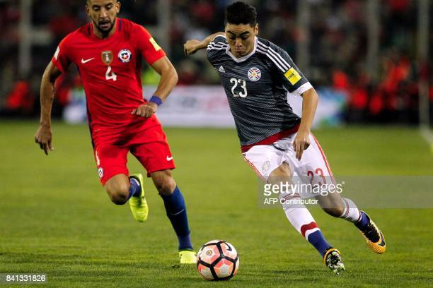 Chile's Mauricio Isla marks Paraguay's Miguel Almiron during their 2018 World Cup qualifier football match in Santiago on August 31 2017 / AFP PHOTO...