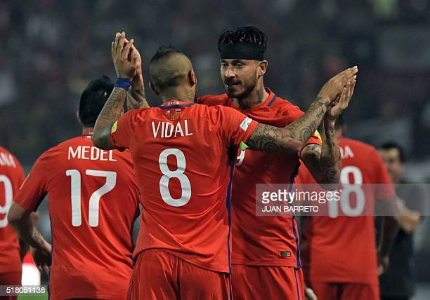 Chile's Mauricio Pinilla celebrates with teammate Arturo Vidal after scoring against Venezuela during their Russia 2018 FIFA World Cup South American...