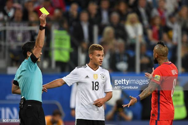 Chile's midfielder Arturo Vidal argues with Germany's defender Joshua Kimmich as Vidal receives a yellow card from Serbian referee Milorad Mazic...