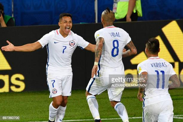 Chile's midfielder Arturo Vidal celebrates with Chile's forward Alexis Sanchez and Chile's forward Eduardo Vargas after scoring a goal during the...