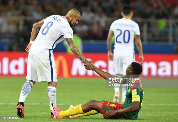 TOPSHOT Chile's midfielder Arturo Vidal helps Cameroon's forward Benjamin Moukandjo stand up after a fall during the 2017 Confederations Cup group B...