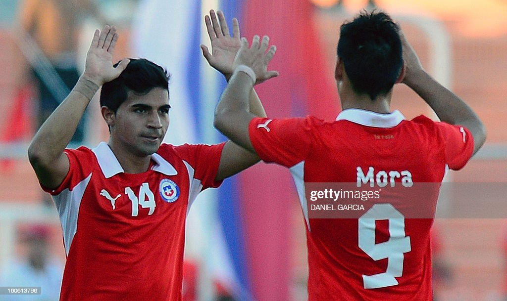 Chile's midfielder Bryan Rabello (L) celebrates with teammate forward Andres Mora after scoring against Peru, during their South American U-20 final round football match at Malvinas Argentinas stadium in Mendoza, Argentina, on February 3, 2013. Four South American teams will qualify for the FIFA U-20 World Cup Turkey 2013.