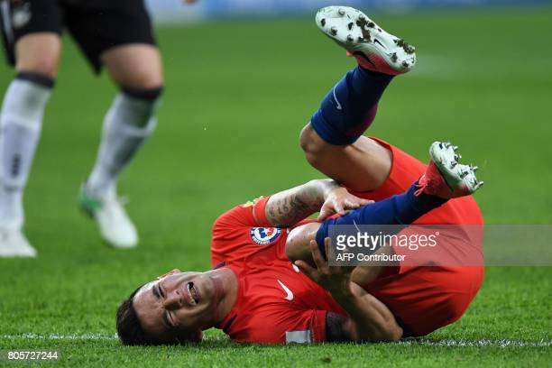 Chile's midfielder Charles Aranguiz holds his knee during the 2017 Confederations Cup final football match between Chile and Germany at the Saint...