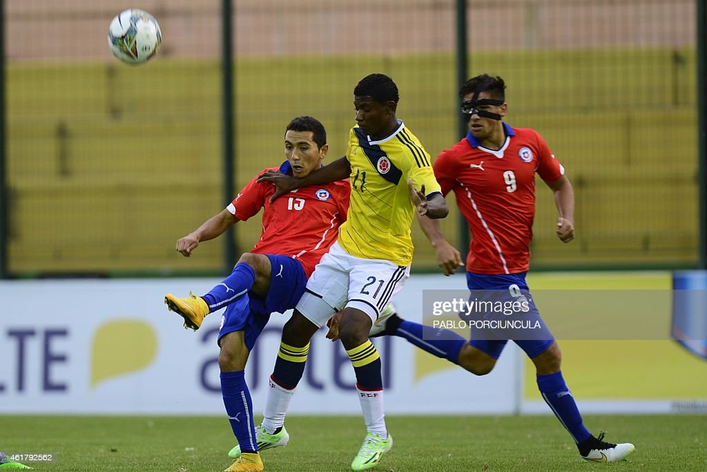 Chile's midfielder Cristian Cuevas (L) tries to control the ball marked by Colombia's defender Luis Orejuela (C) as Chile's defender Camilo Rodriguez looks on during the South American U-20 football match at Domingo Burgueno stadium in Maldonado, 130 km east of Montevideo, on January 19, 2015.