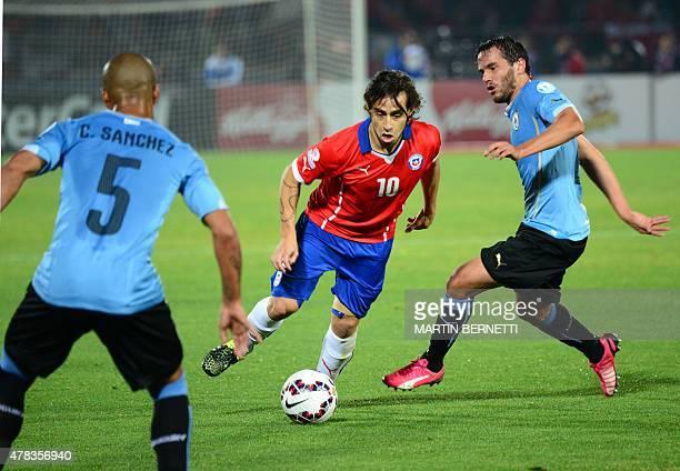 Chile's midfielder Jorge Valdivia is marked by Uruguay's midfielders Alvaro Gonzalez and Carlos Sanchez during their 2015 Copa America football...