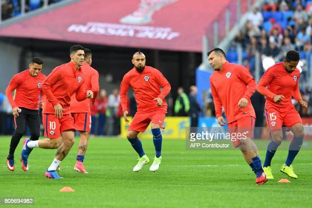 Chile's midfielder Pablo Hernandez midfielder Arturo Vidal and defender Gary Medel warm up prior to the start of the 2017 Confederations Cup final...