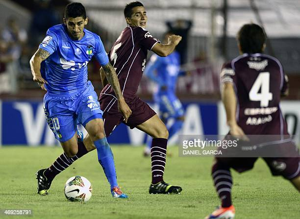 Chile's O'Higgins midfielder Pablo Hernandez vies for the ball with Argentina's Lanus' midfielder Diego Gonzalez and defender Carlos Araujo during...