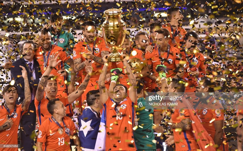 TOPSHOT - Chile's players celebrate with the trophy after winning the Copa America Centenario final by defeating Argentina in the penalty shoot-out in East Rutherford, New Jersey, United States, on June 26, 2016. / AFP PHOTO / Nicholas Kamm
