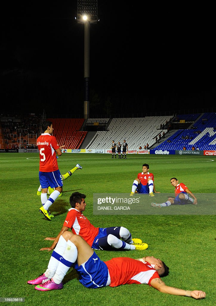 Chile's players rest during an interruption due to a power outage during their football match against Bolivia at Malvinas Argentinas stadium in Mendoza, Argentina, on January 11, 2013 for the qualifying stage of the Group A South American U-20 football tournament. Four teams will qualify for the FIFA U-20 World Cup Turkey 2013. AFP PHOTO / DANIEL GARCIA