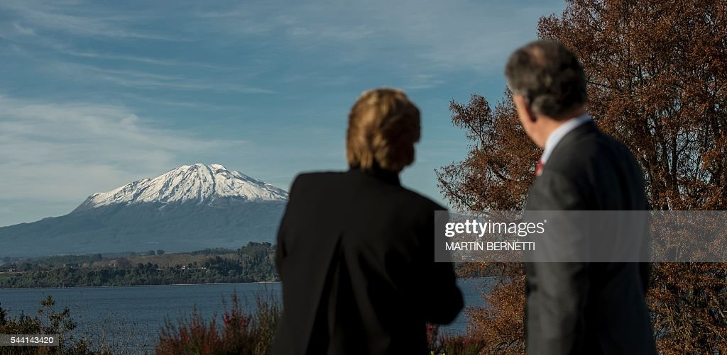 Chile's President Michelle Bachelet (L) and Colombia's President Juan Manuel Santos watch the Calbuco Volcano before posing for the official picture of the XI Pacific Alliance Summit in Puerto Varas, 1150 km south of Santiago, Chile, on July 1, 2016. / AFP / Martin BERNETTI