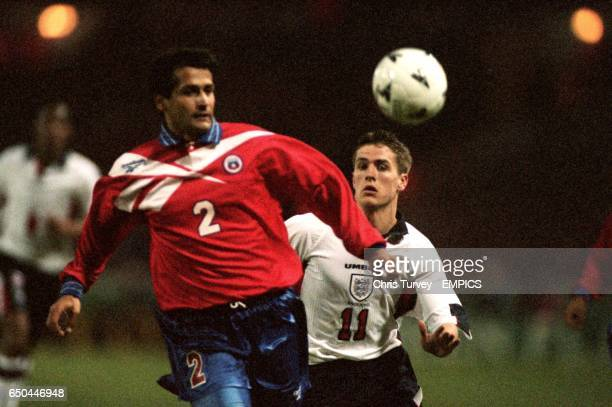 Chile's Ronald Fuentes Left beats England's Michael Owen to the ball