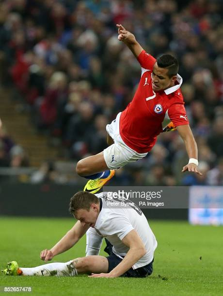 Chile's Sanchez Alexis goes flying after a challenge by England's Phil Jones