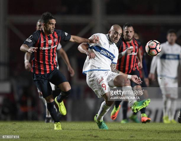 Chile's Universidad Catolica forward Santiago Silva vies for the ball with Argentina's San Lorenzo defender Matias Caruzzo during their Copa...
