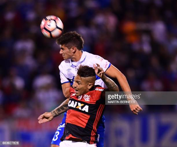 Chile's Universidad Catolica Guillermo Maripan vies for the ball with Brazil's Flamengo Paolo Guerrero during their Libertadores Cup football match...
