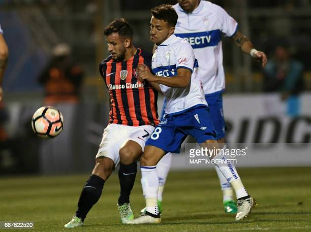 Chile´s Universidad Catolica player Jaime Carreno vies for the ball against Argentinas San Lorenzo footballer Franco Mussis during their Copa...
