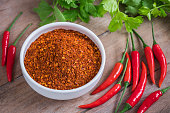 Chili cayenne in bowl and fresh chili on wooden table