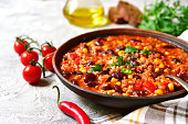 Chili con carne in a clay bowl on a concrete or stone background- traditional dish of mexican cuisine.