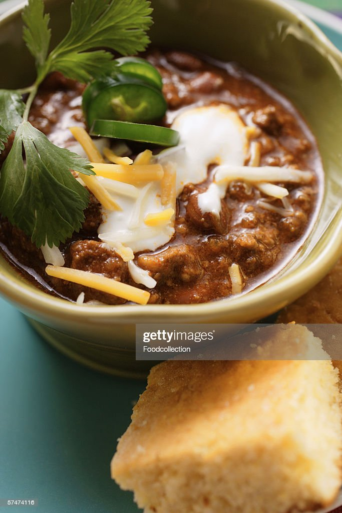 Chili con carne with cheese and sour cream; corn bread : Stock Photo