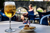 Closeup of cold glass of beer and appetizers on outdoors bar table, with Roman bridge in the background; selective focus.