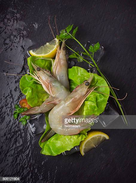 Chilled raw prawn and vegetables on moody black stone background.