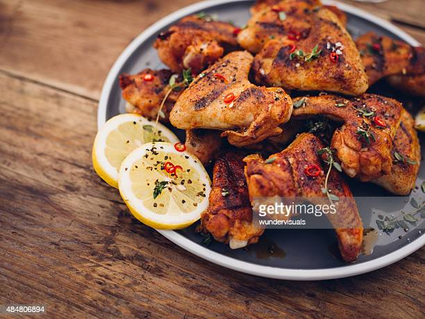 Chillie sprinkled spicy chicken wings on a wooden table