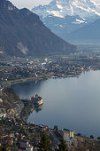 Rochers de Naye, Switzerland. March 29th, 2014. The Chillon Castle (Château de Chillon) and the Lake Geneva (Lac Lemán) viewed from Rochers de Naye promenade. In the Back, the Swiss Alps covered in sn