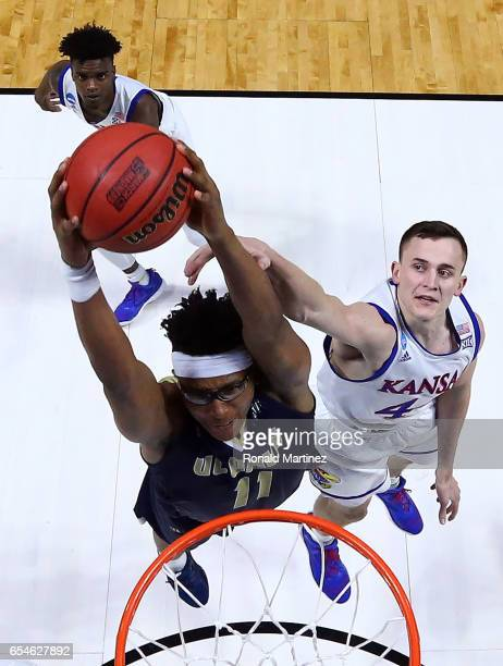 Chima Moneke of the UC Davis Aggies makes a slam dunk against Mitch Lightfoot of the Kansas Jayhawks during the first round of the 2017 NCAA Men's...