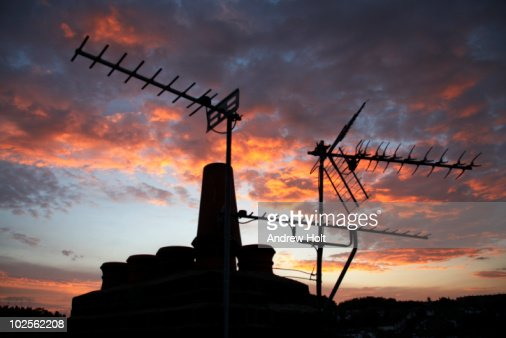 Chimney and television aerial in sunset