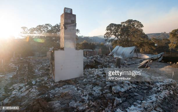 A chimney is seen standing amidst burned out remains at a property near the town of Mariposa California on July 18 2017 The Detwiler fire is...