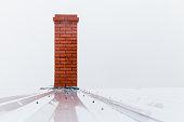 Chimney made of red bricks over foggy white sky