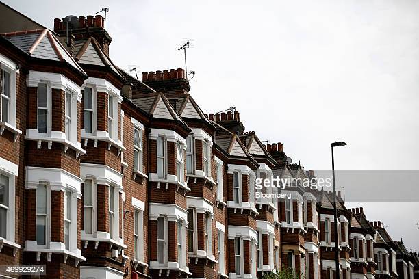 Chimney pots and television aerials stand above the tiled rooftops of residential properties in the Clapham district of London UK on Thursday April...