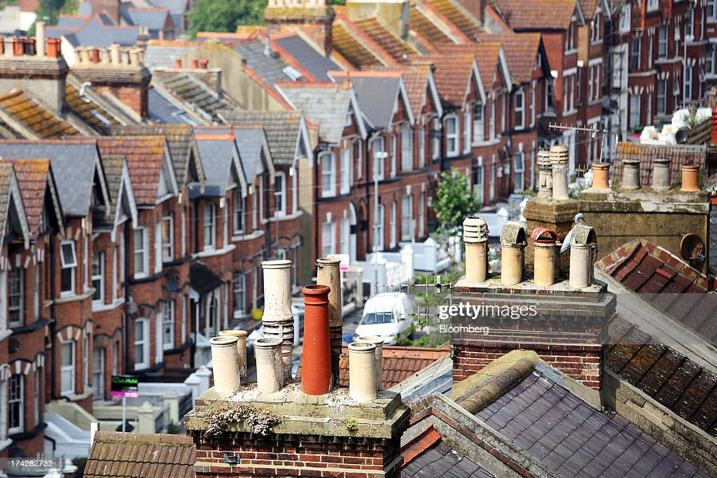 Chimney pots sit atop the roofs of residential houses in the town of Hastings, U.K., on Tuesday, July 23, 2013. U.K. retail sales rose for a second month in June as discounts at department stores drove demand for clothes and electrical products. Photographer: Chris Ratcliffe/Bloomberg via Getty Images