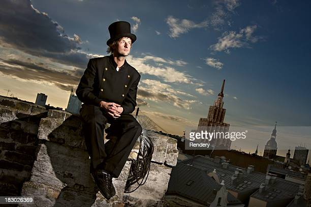 Chimney sweep sitting on the roof with city in background