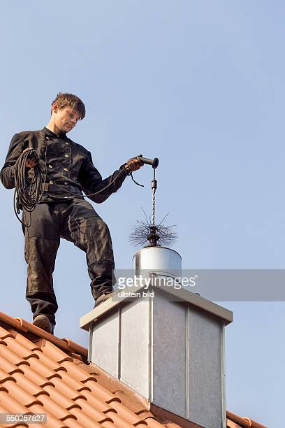 Chimney sweeper cleaning a chimney