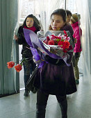 DANDONG China A woman with a bouquet of flowers heads for an international train bound for Pyongyang at Dandong station China on Dec 22 following...