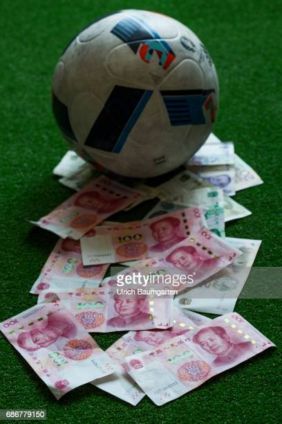 China and its worldwide transfer activities on the football market The photo shows a football and Chinese renminbi banknotes