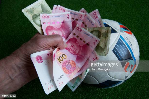 China and its worldwide transfer activities on the football market The photo shows a hand with Chinese renminbi banknotes on a football