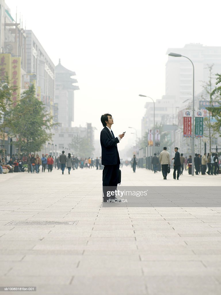 China, Beijing, business man standing in square, holding mobile phone : Stock Photo