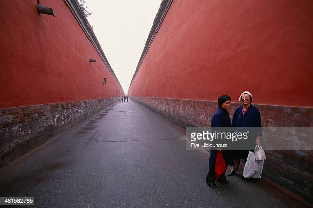 China Beijing Imperial Palace Two women standing between red walls