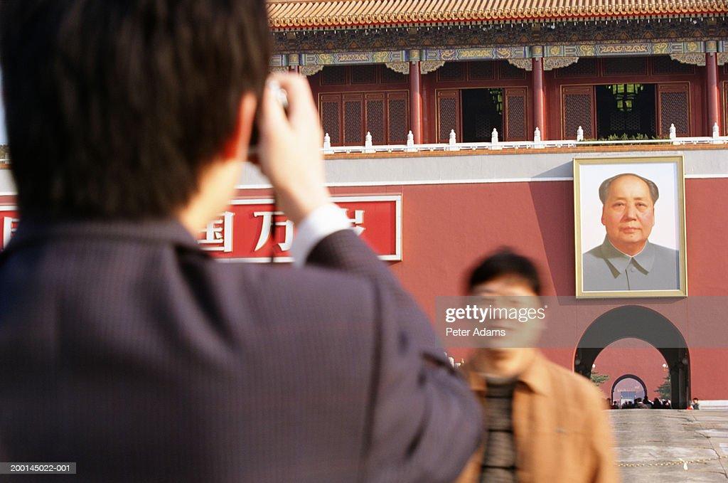China, Beijing, Tiananmen Square, man taking photograph of friend : Stock Photo
