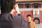 China, Beijing, Tiananmen Square, man taking photograph of friend